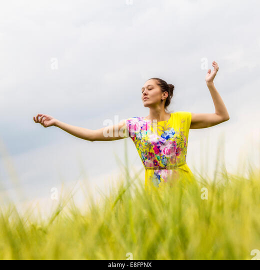 Woman in yellow dress dancing in field - Stock Image