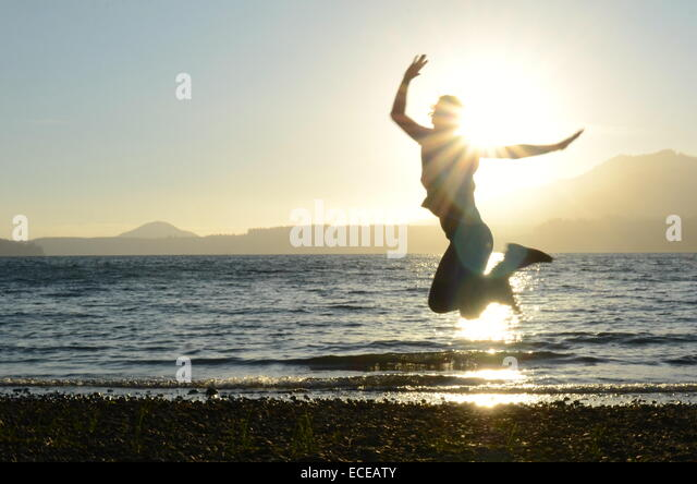 USA, Washington State, Olympic National Park, Action shot of silhouette of woman jumping on beach at sunset - Stock Image