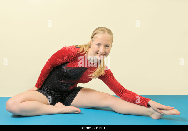 Young woman wearing a velvet leotard doing stretching exercises - Stock Image