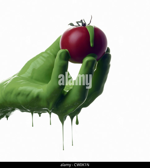 Green painted hand holding tomato - Stock Image