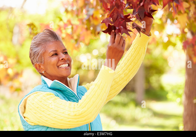 Mature Woman Relaxing In Autumn Landscape - Stock Image