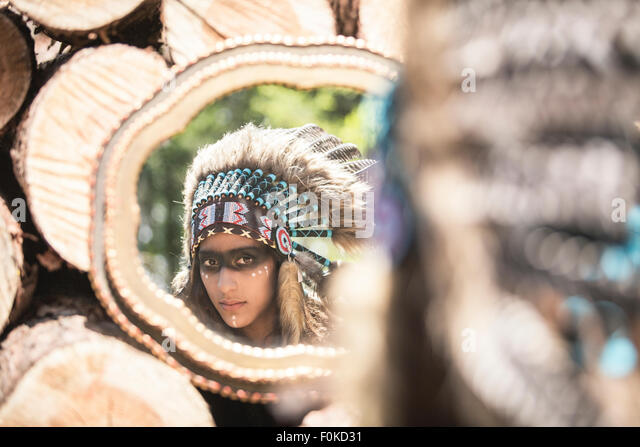 Mirror image of young woman masquerade as an Indian - Stock-Bilder