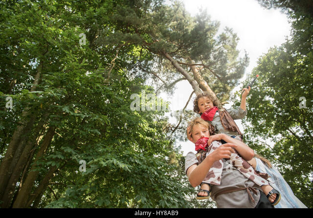 A young boy lifts up his friend whilst playing games in the sunshine - Stock Image