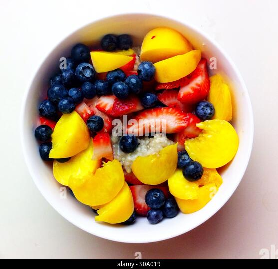 Summery oatmeal covered with colorful fruits and berries - Stock-Bilder