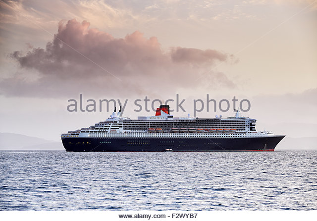 The Queen Mary 2 Ocean Liner leaving Oban at Sunset. - Stock Image