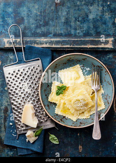 Ravioli pasta with mozzarella cheese, basil and parmesan on blue background - Stock Image