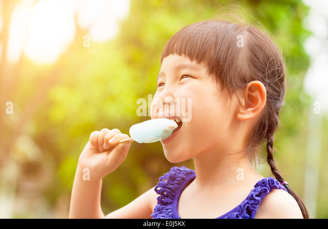happy little girl eating popsicle at summertime with sunset - Stock Image