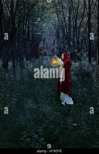 woman with lantern in forest and castle - Stock-Bilder