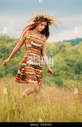 Woman walking in field - Stock-Bilder