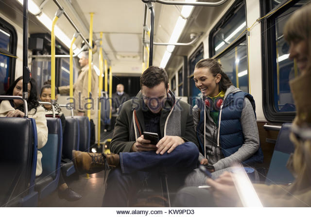 Smiling young couple commuters texting with smart phone on bus - Stock Image