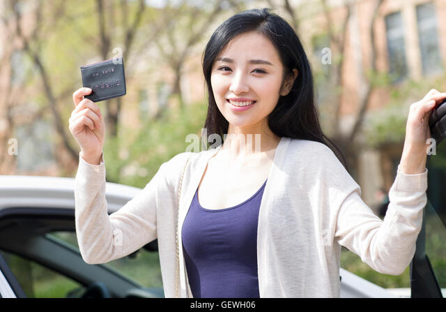Young Chinese woman showing her driver's license - Stock Image