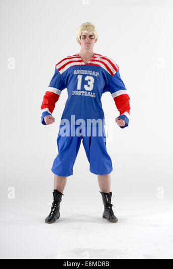 man in fancy dress comedy costume as an american football player with full sports kit - Stock Image