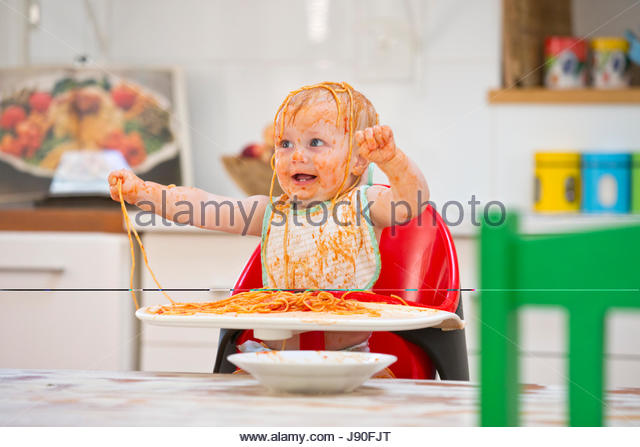 Messy Baby Boy Sits In High Chair Covered In Spaghetti And Sauce - Stock-Bilder
