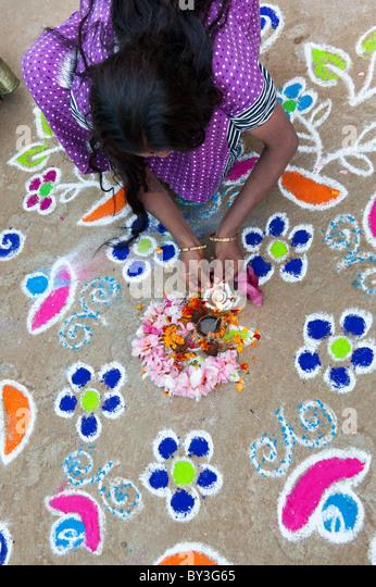 India woman making a Rangoli festival coloured powder design in an Indian street. Puttaparthi, Andhra Pradesh, India - Stock-Bilder