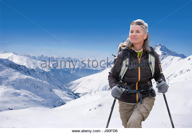 Mature Woman Hiking Through Snow Covered Mountains - Stock-Bilder