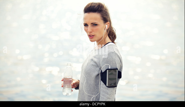 Female runner with bottled water tired from running - Stock Image