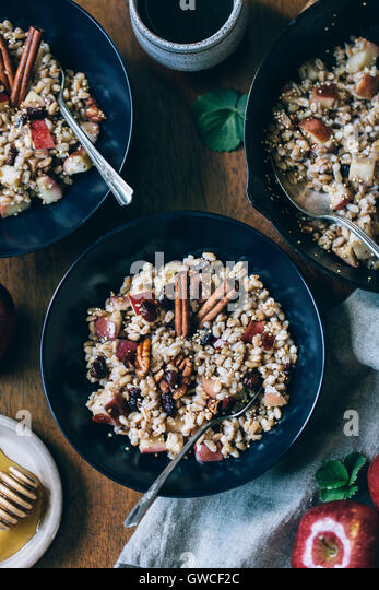 Two bowls of warm farro breakfast bowl are photographed from the top view. - Stock Image