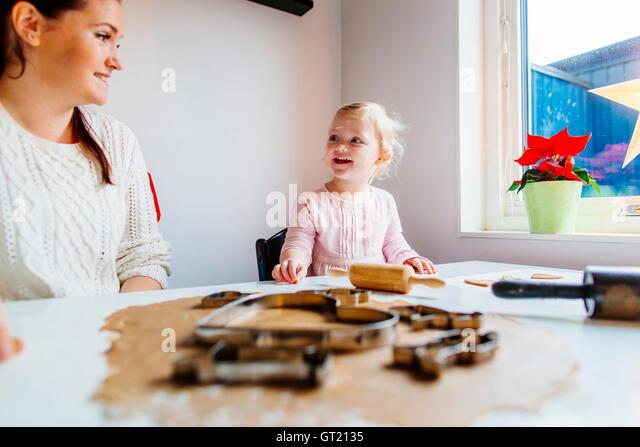 Smiling daughter talking to mother while preparing cookies - Stock-Bilder