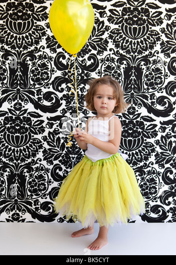 Little girl with yellow tutu and balloon - Stock Image