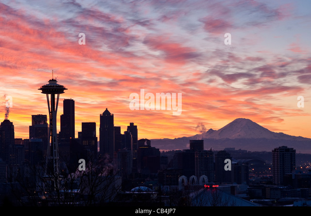 Seattle skyline with Space Needle and downtown buildings at sunrise with dramatic clouds and Mount Rainier Seattle - Stock Image