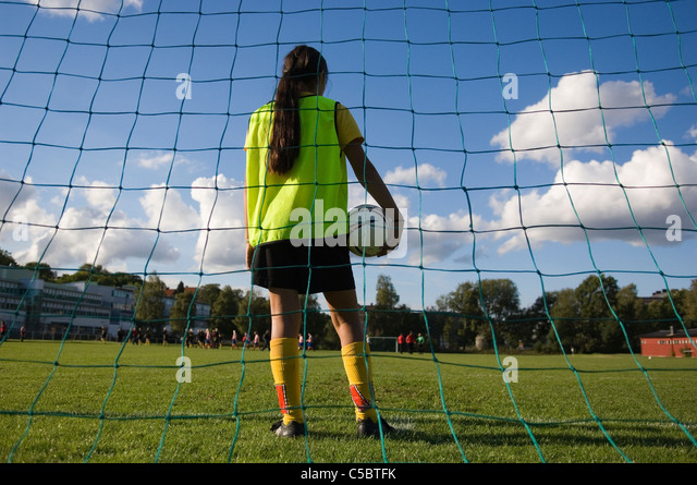 Rear view of a female soccer goalie with ball on the pitch - Stock Image