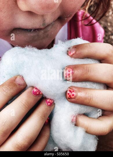 Little girl eats cotton candy with dirty hands and painted fingernails. - Stock Image