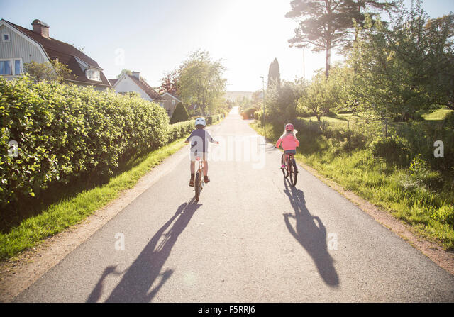 Sweden, Vastergotland, Lerum, Children (10-11, 12-13) cycling in sunny day - Stock Image