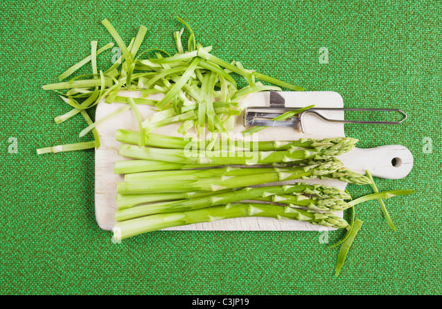Peeled green asparagus on chopping board with peeler - Stock Image