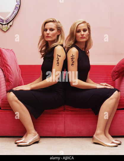 Two women with love and hate tattoos - Stock Image
