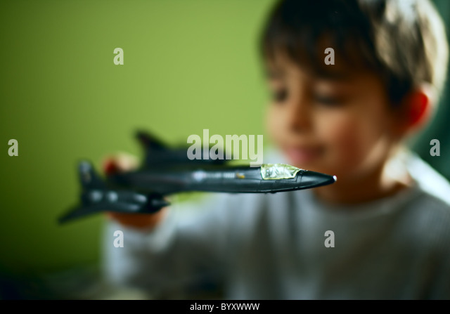 Boy with Blackbird spy plane toy - Stock Image
