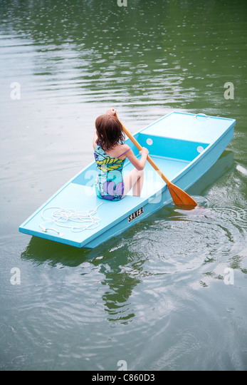 Little girl in small blue row boat - Stock Image