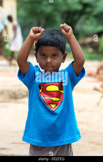 Young Indian boy wearing a superman t shirt in a rural indian village. Andhra Pradesh, India - Stock Image