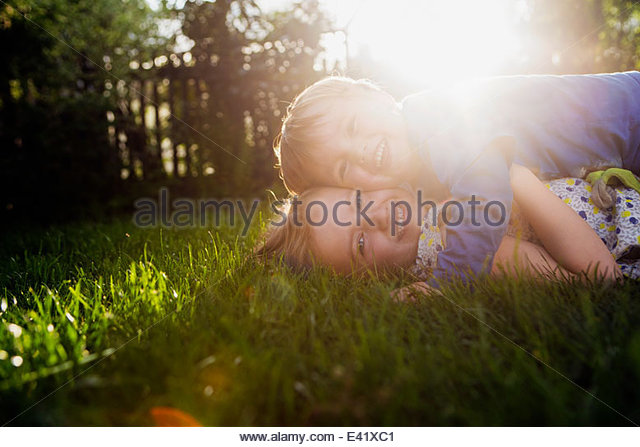 Brother and sister lying on grass, hugging - Stock Image