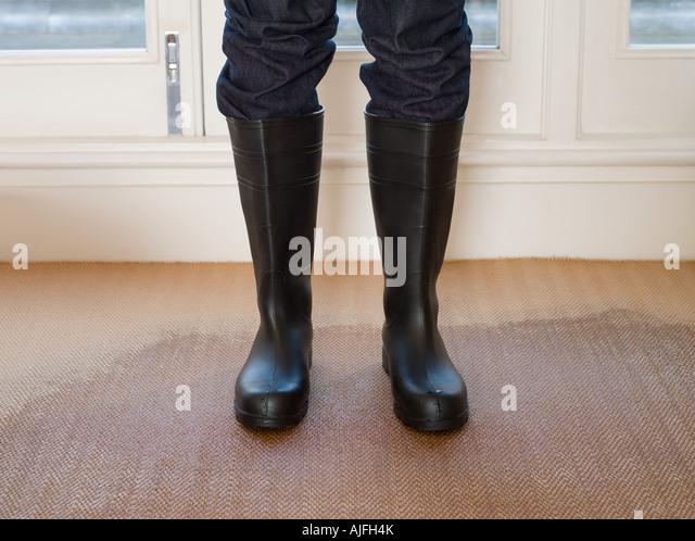 Person wearing rubber boots on a wet carpet - Stock-Bilder