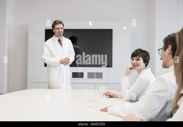 Man wearing lab coat standing in conference room, three people sat at table - Stock Image