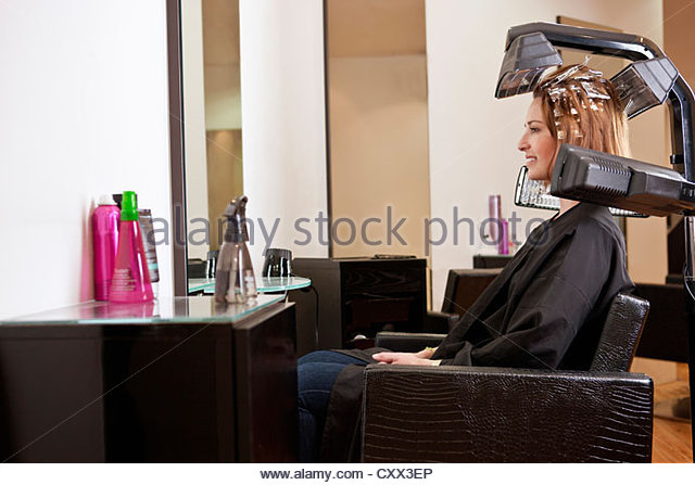 A female client looking at herself in a mirror in a hairdressing salon - Stock Image
