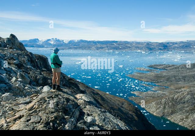 Hiker looking across Sermilik Fjord from the Tiniteqilâq ridge, East Greenland - Stock Image