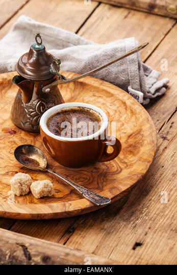 Cup of black coffee and Turkish Cezve on wooden background - Stock Image