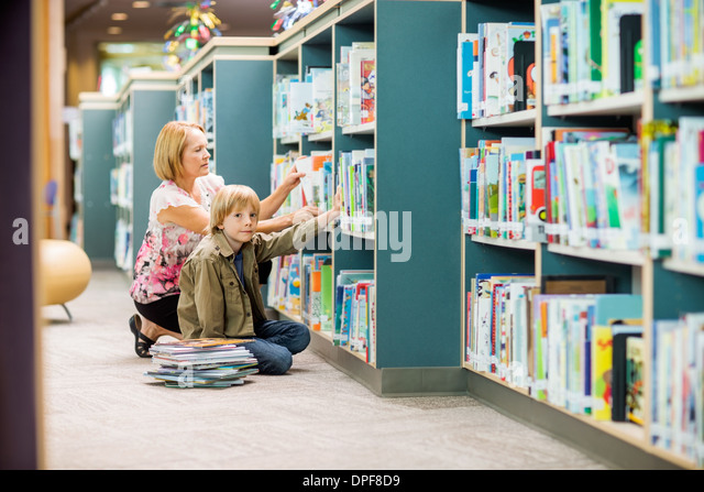 Boy With Teacher Selecting Books From Bookshelf - Stock Image