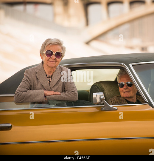 Portrait of cool senior couple with their classic automobile - Stock-Bilder