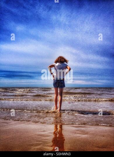 Young girl paddling in sea - Stock Image