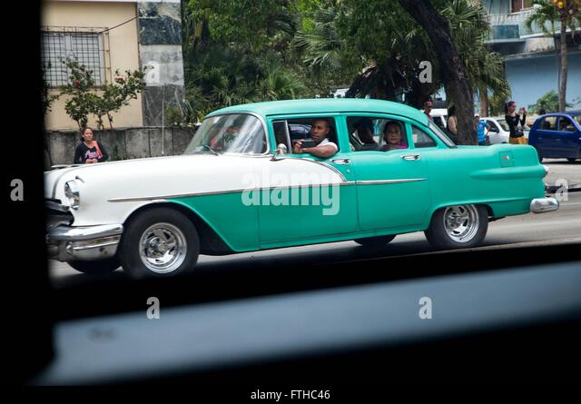 A vintage American car driven by a Cuban family watches as the motorcade of U.S President Barack Obama drives past - Stock Image