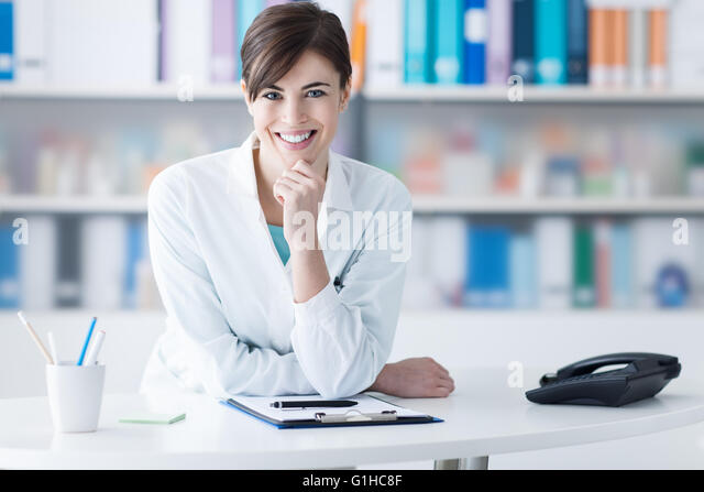 Attractive young female doctor leaning on the clinic reception desk with hand on chin, she is smiling at camera, - Stock Image