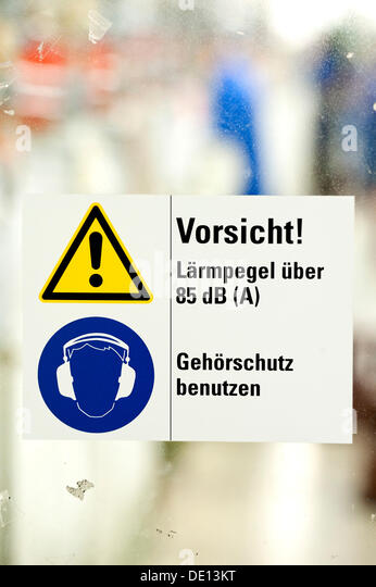 Sign in German, Caution noise levels above 85 dB, use hearing protection, company guidelines for use of hearing - Stock Image