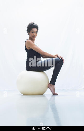 Young woman sitting on fitness ball - Stock Image
