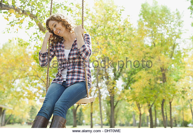 Happy mid adult woman swinging at park during autumn - Stock Image