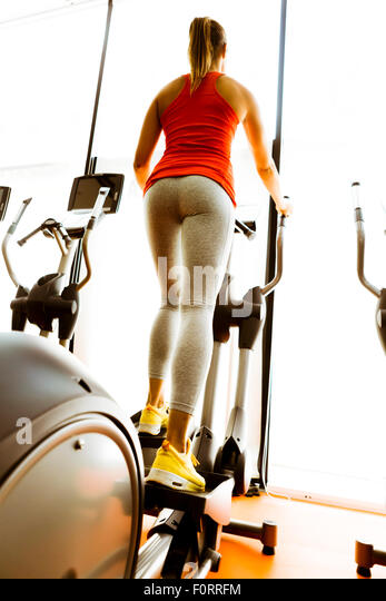 Closeup of a woman using a stepper and training in a fitness center - Stock Image
