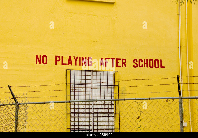 Belize City sign No Playing After School in schoolyard with barb wire fence irony odd unusual - Stock Image