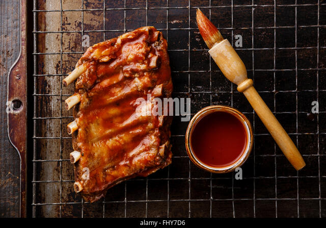 BBQ grilled smoked pork ribs and sauce brush on dark metal baking sheet background - Stock Image