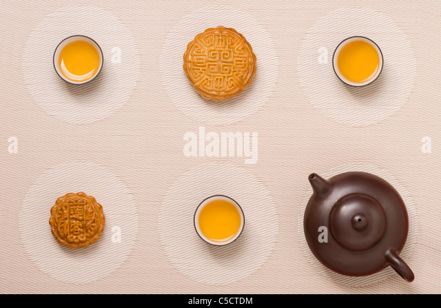 Moon Cakes with Tea on Geometric Place Mat - Stock Image